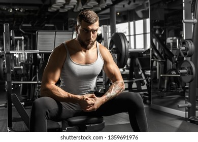 Bearded man bodybuilder sitting on bench at gym looking forward motivated