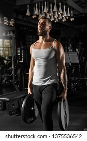 Bearded man bodybuilder standing at gym holding weight plates head up confident