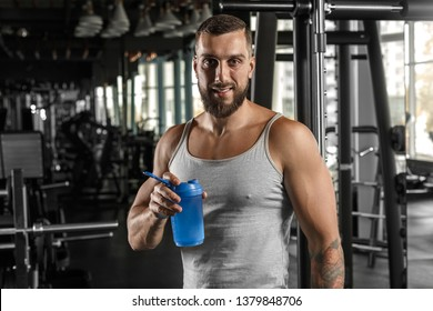 Bearded man bodybuilder standing at gym holding water bottle drinking protein shake looking camera smiling cheerful