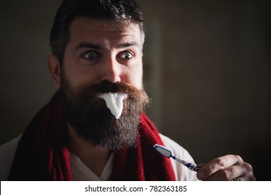 Bearded man brushing teeth with a toothbrush in front of the bathroom mirror in morning. Handsome cheerful man with toothpaste on beard and smiling. How to wake up in the morning to go work?