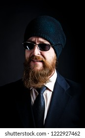 bearded man businessman middle-aged in black sunglasses and a black knitted hat looks with a reproachful and ironic smile. Concept I see right through you.Studio shot on dark background