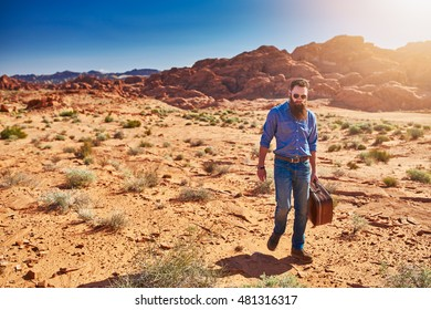 bearded man carrying stuicase through the desert in nevada
