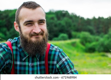 The bearded man in a celltious shirt and red tights with a sincere smile.