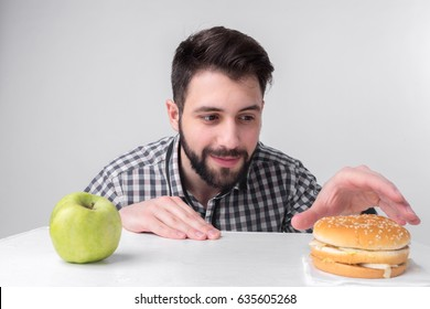 Bearded man in checkered shirt on a light background holding a hamburger and an apple. Guy makes the choice between fast and healthy food. Tasty or useful The dilemma.