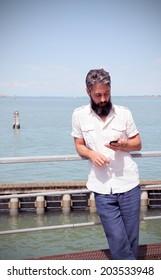 Bearded man checks his smart phone, lagoon on the background