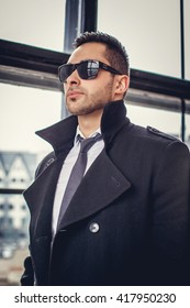 Bearded man in a coat and sunglasses