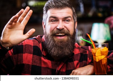 Bearded man cocktail. Portrait man, drinking orange juice. Cheerful bearded man, drink cocktails and smile. Tropical alcoholic fresh cocktail. Barman in pub or restaurant.