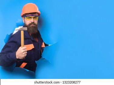 Bearded man in construction helmet makes repair. Builder in hard hat through hole in paper with hammer. Carpenter with hammer. Construction worker in hardhat. Home renovation. Repair home. Copy space.
