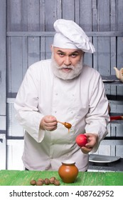 Bearded man cook in chef hat with apple nuts and honey on wooden background