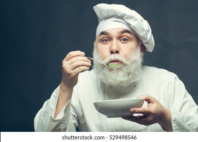 Bearded man cook in hat tasting food with spoon in studio on grey background