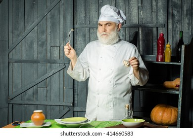 Bearded man cook in studio preparing food with sauce on wooden background