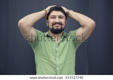 bearded man with cool mustache in green shirt. Smiling happy man relaxing