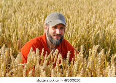 a bearded man in a cup sitting in a wheat field