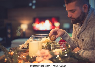 Bearded man decorating christmas table with bubbles