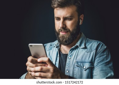 Bearded man in denim jacket using smartphone in everyday life. Modern lifestyle of digital specialists. Guy with wireless earphones listening to music online. Male person taking selfie on smartphone.