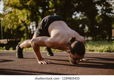 Bearded man doing dive bomber push ups in outdoor gym with face down on a sunny day