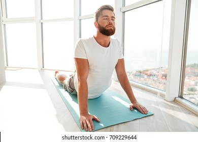 Bearded man doing yoga exercise over window background at home