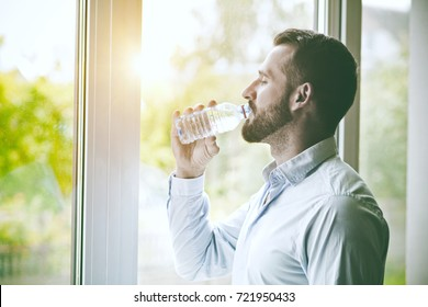 bearded man drinking bottle of water