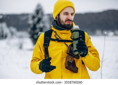 Bearded man drinks hot beverage from the thermos and makes an ugly face somewhere in the mountains covered with snow