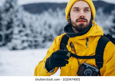 Bearded man drinks hot beverage from the thermos somewhere in the mountains covered with snow and enjoys the view