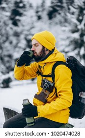 Bearded man drinks hot beverage from the thermos somewhere in the mountains covered with snow