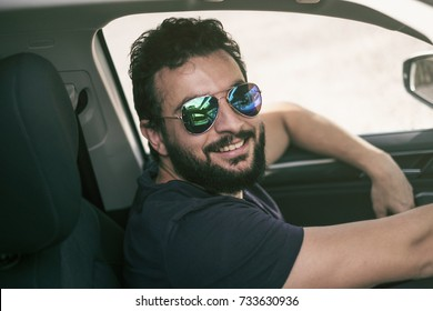 Bearded man driving car and smile looking at camera with sunglasses