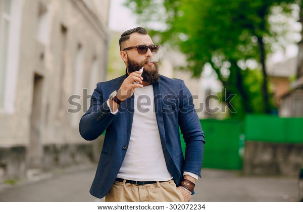 bearded man with e-cigarette outdoors