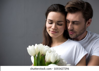 Bearded man embracing attractive brunette wife with bouquet of tulips