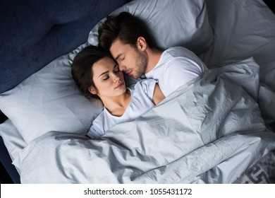 Bearded man embracing attractive brunette woman while sleeping in bed