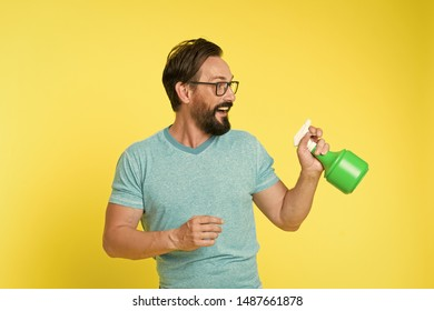 Bearded man with eyeglasses refresh sprinkling water. Man refresh with spray bottle yellow background. Time to refresh yourself. Heat season. Hot and thirst. On guard of freshness. Refresh concept.