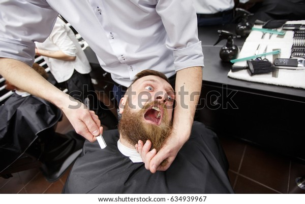 Bearded man with fear is sitting in a Barbershop.