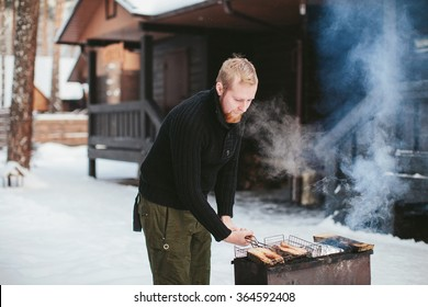 bearded man a fish fry on the grill in the winter forest