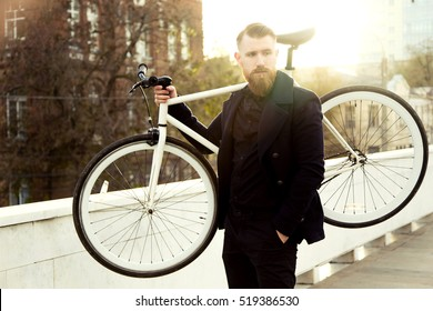 Bearded man with a fixie bicycle. Low angle view of confident young bearded man carrying his bicycle on shoulder and looking away while walking outdoors. stylish businessman with a bike.