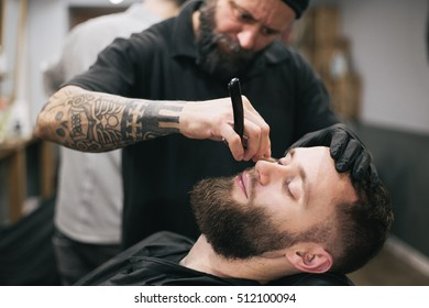 Bearded man getting his hair and beard cut at the local barber shop