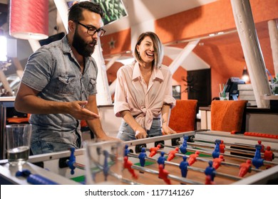 Bearded man with a girl playing table football in a bar