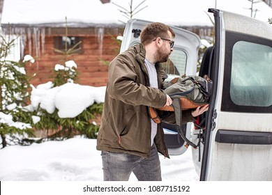 Bearded man in glasses puts things in the trunk of a car, against a background of snow-covered trees and a wooden house, on a winter day.