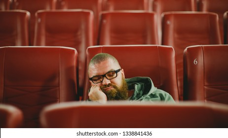 Bearded man with glasses sleeping alone in cinema hall while everyone is gone