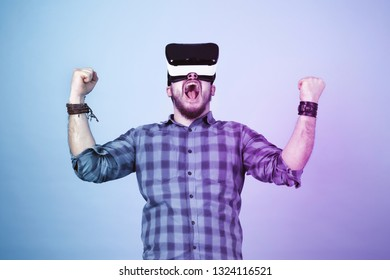 bearded man in glasses of virtual reality (VR device), rejoices victory with enthusiastic emotion, blue and magenta toned