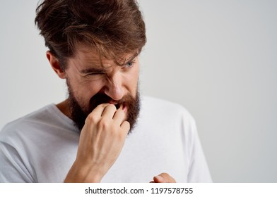 bearded man gnaws his fingers
