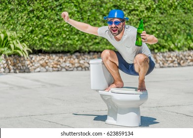The bearded man in goggles astride the toilet, which is installed in the middle of the street. Toilet brush in his hand, cooking pan on his head. Drinking beer