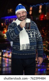 Bearded man is going to chug a pitcher of dark beer as fast as he can. Middle-aged man wears winter sweater, white scarf and Santa Claus blue hat. He is posing on street sparkling blurred background