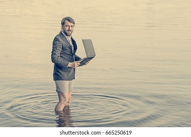 Bearded man in a gray jacket and underwear with a laptop in hands standing knee-deep in water. Toned