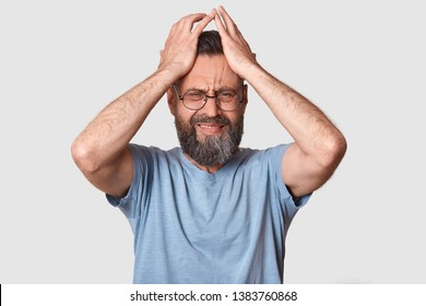 Bearded man in gray t shirt, has round eyewear, keeps hand on head, grimaced, has problems, being in bad mood, has terrible headache, being in conflict wit his wife. People emocions concept.