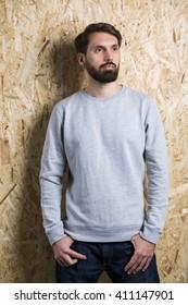 Bearded man in grey sweatshirt on textured light brown background. Mock up