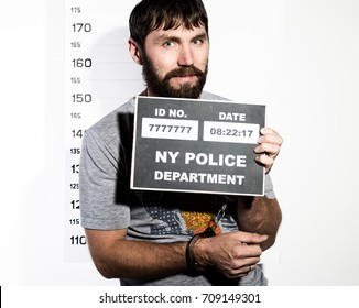 bearded man in handcuffs holds a sign, Criminal Mug Shots