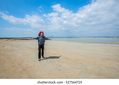 Bearded man, hiker with arms outstretched, enjoying life on the coast of Larnaca salt lake, Cyprus, sunny morning.