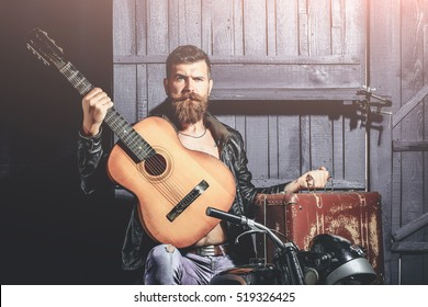 Bearded man hipster biker brutal male with beard and moustache in leather jacket sits on motorcycle with vintage suitcase and guitar on wooden background