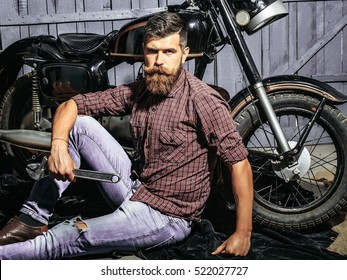 Bearded man hipster biker brutal male with beard and moustache sits on floor near motorcycle with wrench on wooden background