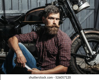 Bearded man hipster biker brutal male with beard and moustache in leather jacket sits on floor near motorcycle with wrench on wooden background