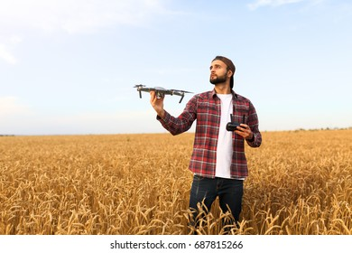 Bearded man hipster shows small compact drone and holds remote controller in his hand. Farmer agronomist looks at quad copter before the launch in a wheat field